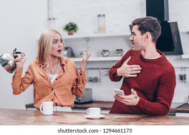 emotional young couple quarrelling in kitchen, mistrust concept
