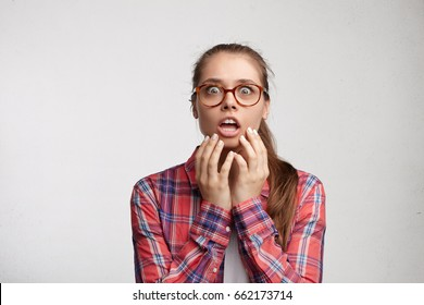 Emotional young female in eyeglasses looking scared touching her chin with both hands looking with great surprise in camera being shocked after hearing horrified news about friend trembling with fear