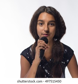 emotional young girl actress brunette with long hair in black dress with microphone on a white background