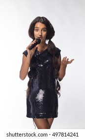 emotional young girl actress brunette in a black dress with a microphone on a white background