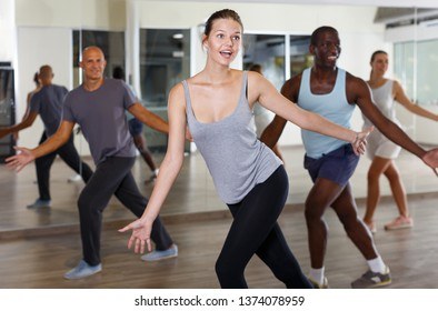 Emotional young girl and men enjoying dance  techniques together in studio
