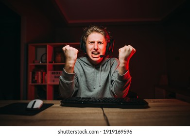 An emotional young male gamer looks angrily at the camera and in despair shows his fists, sits in a room with a red light and gets angry. Aggressive guy playing online computer games at home.