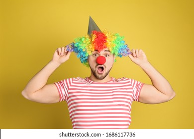 Emotional young man with party hat and clown wig on yellow background. April fool's day
