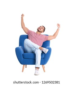 Emotional young man sitting in armchair on white background