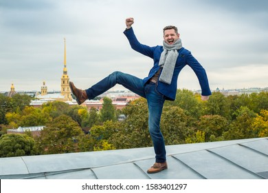 An emotional young man stands on the roof of the building on one leg. Pretending to push the building of the Peter and Paul Cathedral with his foot. Saint-Petersburg, Russia.