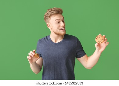 Emotional young man with tasty cookies on color background