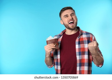 Emotional young man with wallet full of money on color background. Space for text