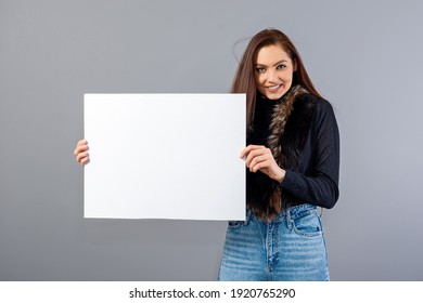 emotional young teenager woman showing blank signboard with copy space, isolated on gray
