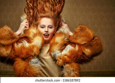 Emotional young woman with beautiful flying red hair posing in a luxurious fox fur coat on a vintage background. Winter beauty fashion. Fur coat style.