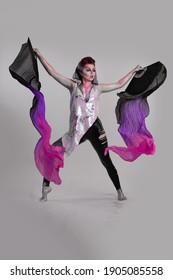 Emotional Young Woman with creative pink purple make-up and with bright fans in her hands posing on a white background in the studio