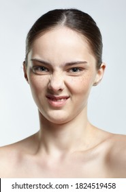 Emotional young woman face portrait with disgust pucker facial expression. Human female natural emotions and expressions concept. Girl with healthy skin and nude makeup posing on white background.