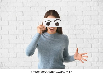 Emotional young woman hiding face behind sheet of paper with drawn eyes against white brick wall
