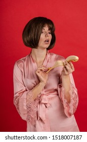 Emotional young woman in a pink silk robe holds bananas in her hands, indulges in and poses on a red background