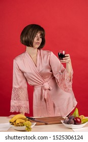 Emotional young woman in a pink silk robe holds a glass of red wine in her hands and poses on a red background