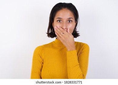 Emotional Young woman with short hair wearing casual yellow sweater isolated over white background gasps from astonishment, covers opened mouth with palm, looks shocked at camera. Reaction con