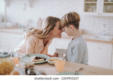 Emotional young woman spending time with her son in the kitchen and smiling while touching his face with her nose