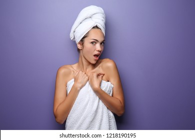 Emotional young woman wrapped in towel on color background