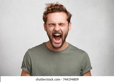 Emotional youngster yells loudly, opens mouth broadly, feels desperate after finding out about tragic events, poses against white studio wall. Caucasian bearded guy scremas in terror of something