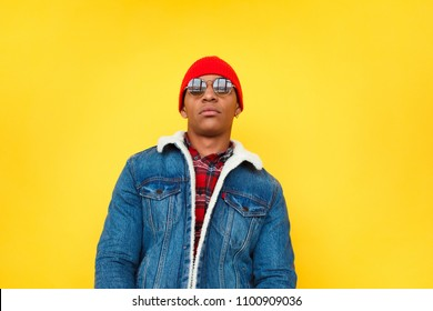Emotionless black man in denim jacket and hat with sunglasses looking at camera against bright yellow.