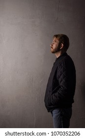 An emotionless portrait of a man in a black jacket and jeans standing near a wall. copy space. deadpan without retouching
