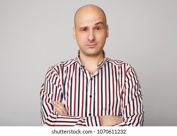 emotions of bald man. Confused middle aged guy wearing shirt isolated over grey studio wall