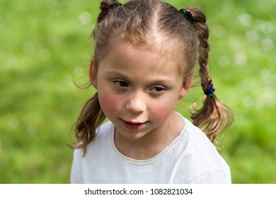 the emotions of a beautiful expressive five-year-old girl with huge green eyes and a haircut in the form of funny plaits on a blurred background of the greenery of the park