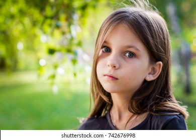 The emotions of a beautiful girl with long hair.  Cute little girl pensive. The girl dreams about something.