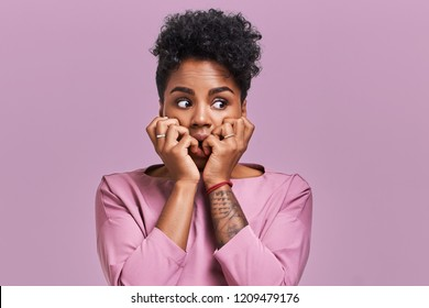 Emotions concept. Nervous emotional scared young lovely African American female stares at camera and opens mouth widely, notices phobia, expresses her fear against something, poses alone indoor