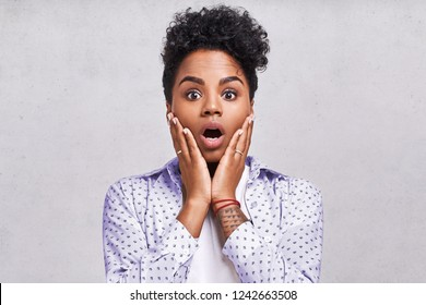 Emotions concept. Nervous emotional scared young lovely African American female stares at camera and opens mouth wide, notices phobia, expresses her fear against something, poses alone indoor.