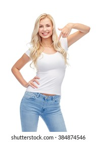 emotions, expressions, advertisement and people concept - happy smiling young woman or teenage girl in white t-shirt pointing finger to herself