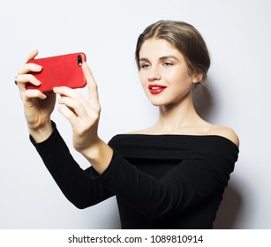 Emotions, expressions and people concept - happy smiling young woman wearing black dress  taking selfie with smartphone