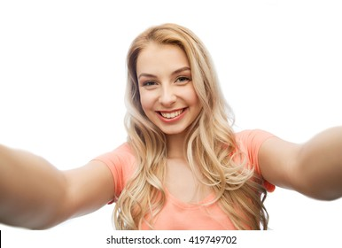 emotions, expressions and people concept - happy smiling young woman taking selfie