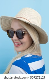 emotions, expressions, summer and people concept - smiling young woman or teenage girl in sunglasses over blue background