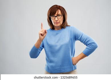 emotions and old people concept - displeased senior woman in glasses warning over grey background