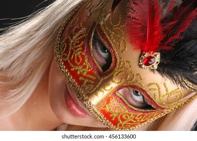 emotions on the face of the girl in the Venetian mask on black background