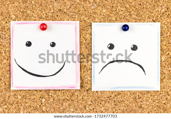 Emotions are painted on notes attached to a cork board, sad and cheerful faces are nearby.
