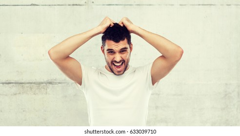emotions, stress, madness and people concept - crazy shouting man rending ones hair in t-shirt over gray stone wall background