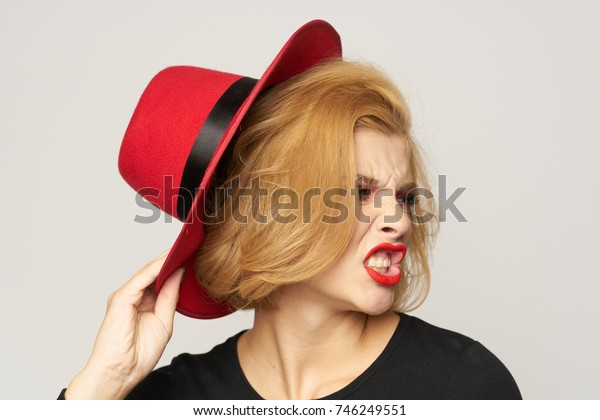 emotions, young, stylish woman in a hat on a light background