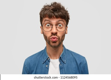 Emotive handsome young guy pouts lips with wonderment, stares through big glasses, has dark stubble, dressed in denim shirt, poses against white background. People, amazement and shock concept