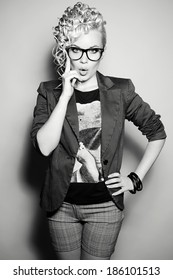 Emotive portrait of a beautiful fashionable hipster girl in trendy eyewear singing a song over light gray background. Shot shot