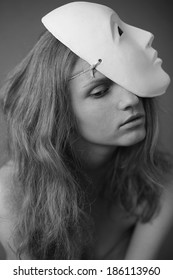 Emotive portrait of a beautiful model with a white mask (volto bianco) on her head. Daylight. Close up. Black and white (monochrome) studio shot