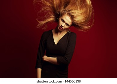Emotive portrait of a beautiful red-haired (ginger) girl with flying hair. Girl with evening make-up and cocktail dress posing over red background. Seductive glance. Copy-space. Studio shot
