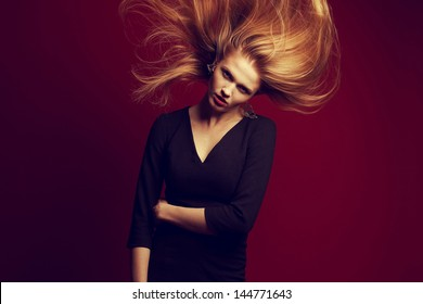 Emotive portrait of a beautiful red-haired (ginger) girl with flying hair. Girl with evening make-up and cocktail dress posing over purple (pink) background. Seductive glance. Copy-space. Studio shot
