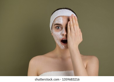 Emotive portrait of beautiful young woman with white mask bare shoulders, having fun, clothing one eye with hand, pretty joyful girl looking at camera isolated on green background