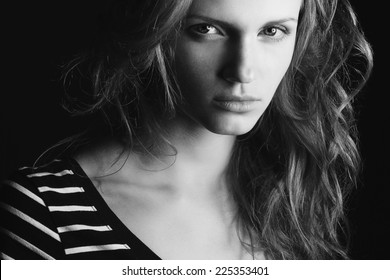 Emotive portrait of fashionable model with curly hair and natural make-up posing over black background. Perfect skin. Retro style. Black and white (monochrome) studio shot