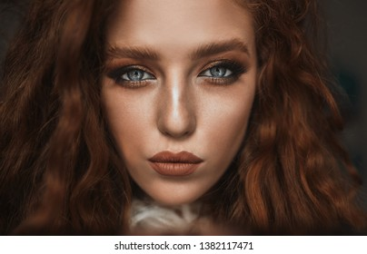 Emotive portrait of a fashionable model with red (ginger) curly hair and natural make-up posing over grey background. Perfect skin with freckles. Studio shot