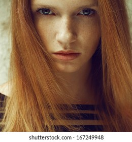 Emotive portrait of a fashionable model with red (ginger) hair and natural make-up. Perfect skin with freckles. Close up. Daylight. Outdoor shot