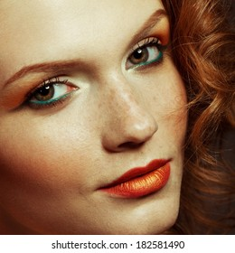 Emotive portrait of a fashionable model with red (ginger) curly hair and arty make-up. Perfect skin with freckles. Retro (disco) style. Close up. Studio shot