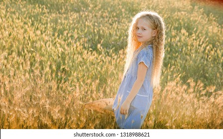 Emotive portrait of a good and calm little blonde girl looking at her mom standing in a field of wheat at sunset. Happy childhood. Summertime. Summer vacation. Positive emotions and energy. Lifestyle