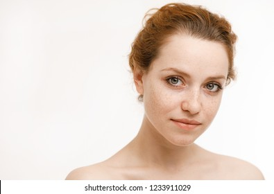 Emotive portrait of a happy and gentle nude beautiful girl with red hair looking into a mirror isolated on white background. Positive emotions and energy. Beauty concept.Lifestyle. Cosmetic procedures